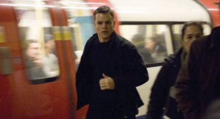 Matt Damon as Jason Bourne doing something spy-esque near a train.